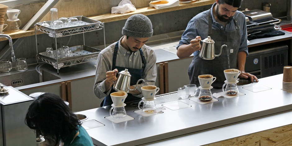 In this April 27, 2015 photo, baristas make coffee at a Blue Bottle Coffee shop in Tokyo. Japan is welcoming American coffee-chain Blue Bottle with long lines that have at times meant a four-hour wait for a cup. This is a nation famous for queuing up for just about anything new in town - pancakes, popcorn, doughnuts, even Taco Bell. (AP Photo/Shuji Kajiyama)